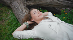 Young, beautiful girl lies on a log in the woods with closed eyes - stock footage