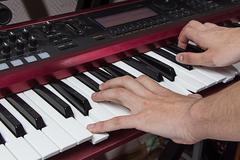 Man playing synthesizer - stock photo