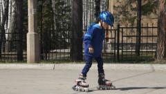 Stock Video Footage of young boy learning to ride on rollerblades in park