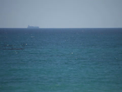 Transportation ship sailing on horizon over water Stock Footage