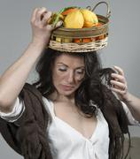 woman with a basket of fruit on her head - stock photo