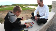 Father and son smiling while playing checkers Stock Footage
