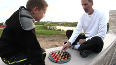 Father and son playing checkers outside Stock Footage