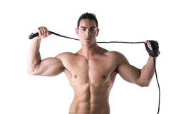 muscular shirtless young man with whip and studded glove - stock photo