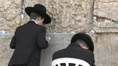 Man sit and pray with his son at the western wall Stock Footage