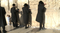 Four orthodox men and kid pray at the western wall in Jeruslaem Stock Footage