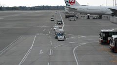 ramp and utility vehicles and trucks driving around parked airplane at narita - stock footage