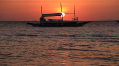 Boat on the sea at sunset in island Malapascua, Philippines Stock Footage