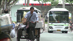 Waste paper collector pedalling directly into camera Stock Footage