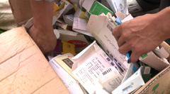 CU hands sorting waste paper and cardboard Stock Footage