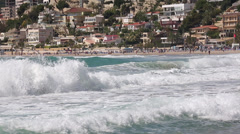 Mediterranean sea waves with a fishing village behind. Stock Footage