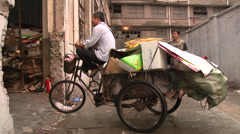Man sits on tricycle laden with waste cardboard Stock Footage
