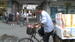 Heavily laden tricycle rides thro' shot Stock Footage