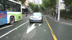 Car crosses junction, tricycle pulls out behind Stock Footage