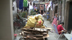 Tricycle in narrow back street, washing hanging out Stock Footage
