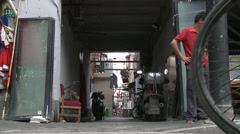 Low shot, laden tricycle enters alley way Stock Footage