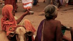 Women beg on a busy street in India. Slow motion. Stock Footage