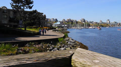 Dolly shot - people walking false creek seawall Stock Footage