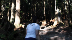 Lady walks the grouse grind - pan up to trees Stock Footage