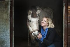 A woman standing next to a grey horse stroking its muzzle, at the stable door. - stock photo