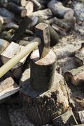 A woodpile, a stack of logs and an axe wedged in a log. Stock Photos