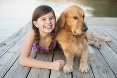 A young girl and a golden retriever dog lying on a jetty. - stock photo