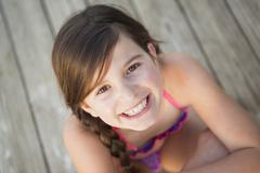 A young girl seated on a jetty looking upwards. - stock photo