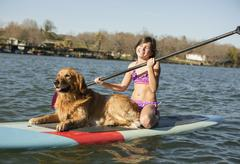 A child and a retriever dog on a paddleboard on the water. - stock photo