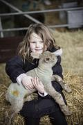 A girl holding a small new-born lamb. - stock photo