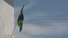 0144 Flag of Brazil on building, bleu sky, electricity cabels, slowmotion Stock Footage
