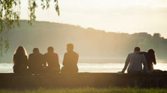 People relax on the beach at sunset Stock Footage