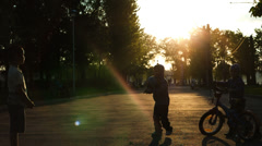 Kids jump at sunset in summer park Stock Footage