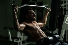 Bodybuilder doing heavy weight exercise for back Stock Photos