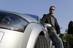 Successful businessman in front of his convertible Stock Photos