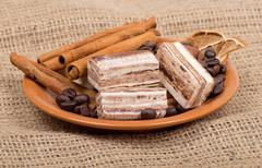 Sweets, cinnamon, nuts and coffee beans on a saucer, on burlap b Stock Photos