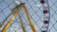 Close up ferris wheel through chainlink fence Stock Footage