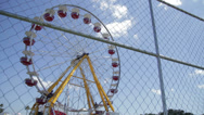 Stock Video Footage of Wide Ferris Wheel Through Chain link Fence