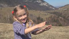 Child Playing with Cricket Bug on Meadow in Mountains, Girl with Insect in Hand - stock footage