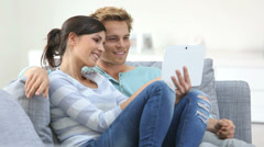 young couple in sofa websurfing on internet with tablet - stock footage