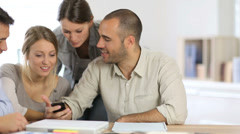 Young people in office playing with smartphone Stock Footage