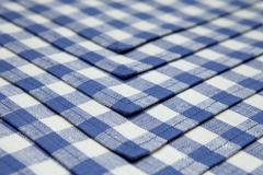 Linen napkins in blue cage lined background. - stock photo