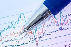 Financial graphs and pen Stock Photos