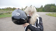 Blond girl on the motorcycle, taking off helmet Stock Footage
