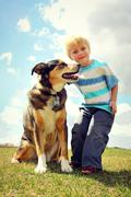 Happy little kid outside with his dog Stock Photos