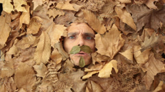 angry autumn man under a bed of falling leaves - stock footage