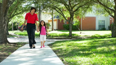 mom walking her little girl home from school slow motion - stock footage