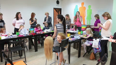 Trainer at the courses for braiding. Mothers with daughters listening and making - stock footage
