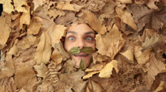 Happy autumn man under a bed of falling leaves Stock Footage