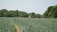Farm tractor field crop spraying fertilizers for better growth Stock Footage