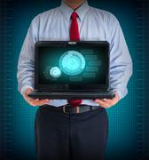 businessman holding a laptop showing business graph - stock photo